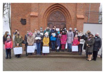 Grupa dzieci stoi przed budynkiem biblioteki