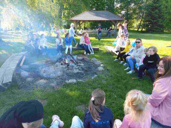 Dzieci siedzą przy ognisku.